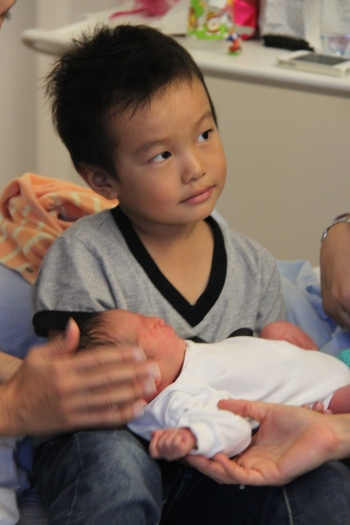 Big brother holding Nathan for the very first time